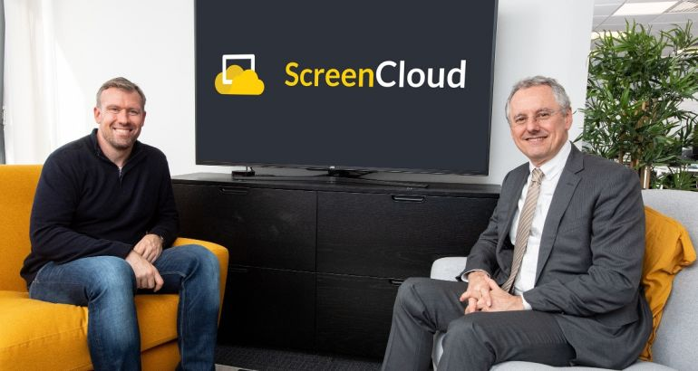 The ScreenCloud CEO is sitting beside the CEO of InvestNI in a modern office space in front of a widescreen TV with the company logo on it.