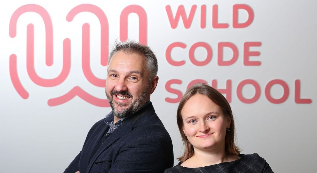 A man and woman are standing back to back and smiling into the camera against a wall with a sign saying Wild Code School.