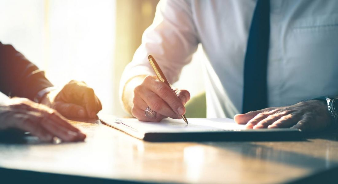 Close-up of a businessman signing a contract on a table with a pen as another businessman looks on.