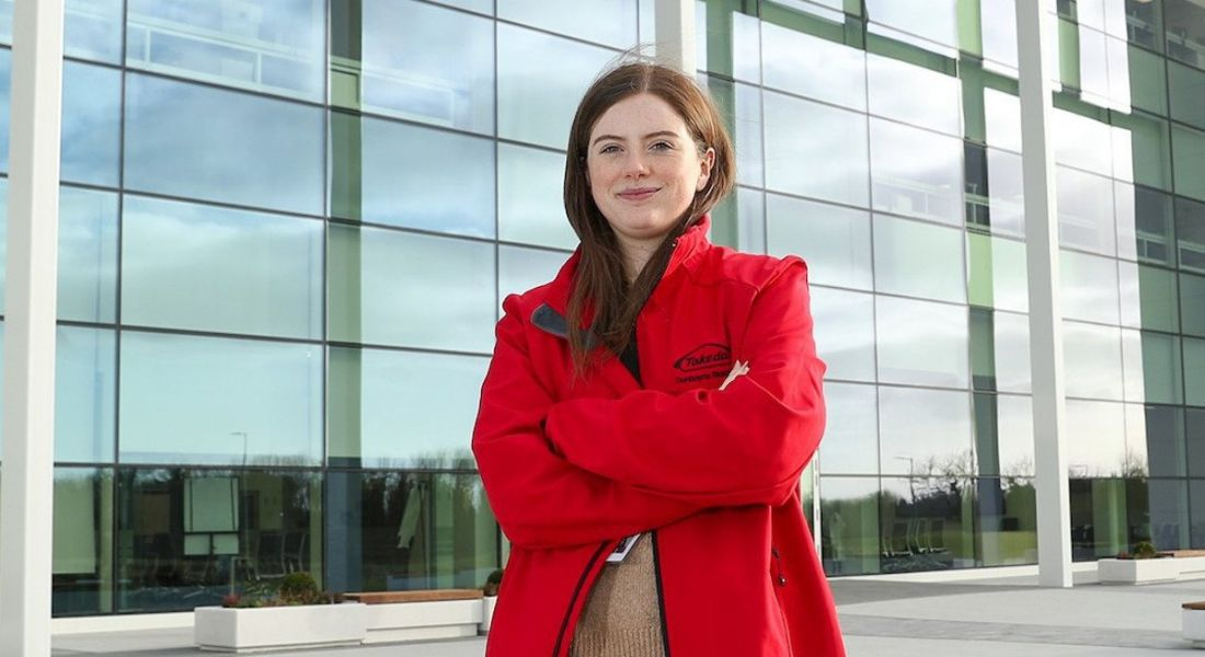 A young professional woman in casual clothing is standing outside the Takeda Dunboyne building, and wearing a red Takeda-branded jacket.