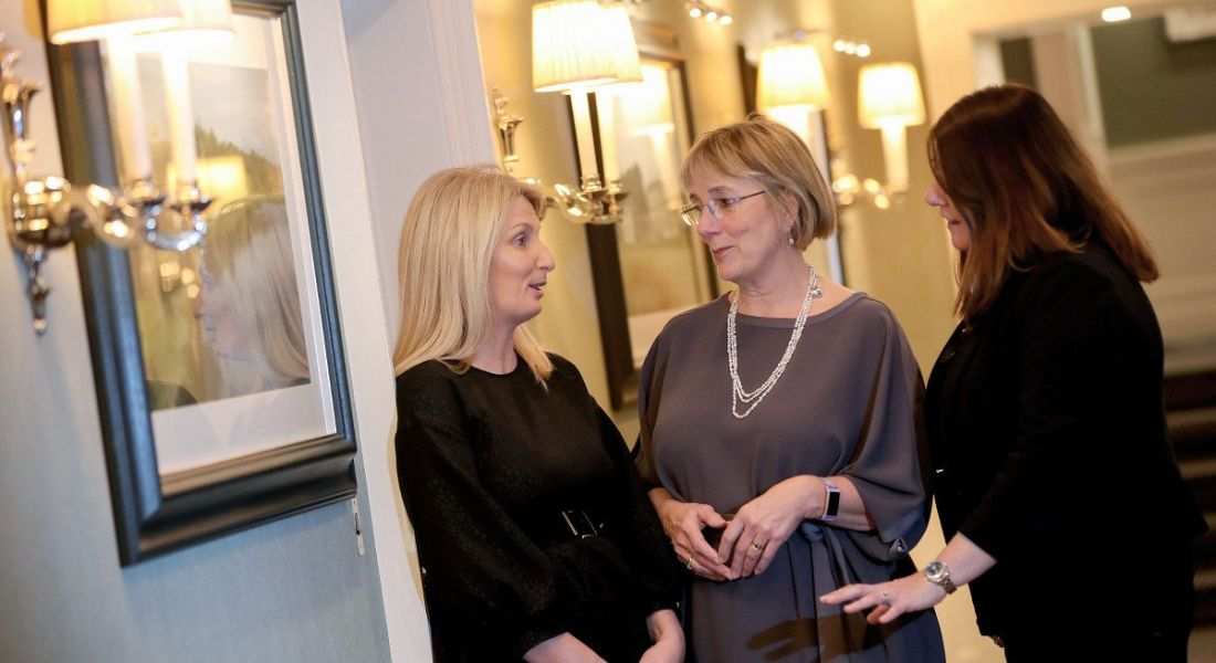Three women stand in conversation in a softly lit hallway with artwork hanging on the walls.