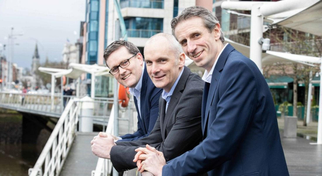 Three professional men from Granite Digital are standing in a row along a river bank in an industrial setting, smiling into the camera.