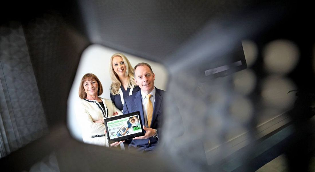 Two professional women and one man are looking into the camera down the barrel of an object. They are holding a tablet showing TechLearn, the new e-learning platform for Irish tech companies.