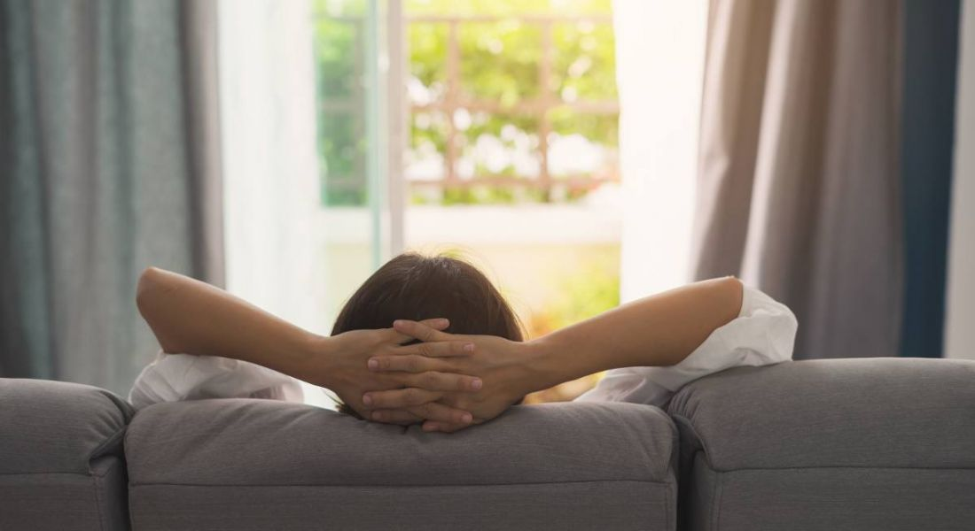 A woman is relaxing on a sofa at home and looking outside while taking a break.