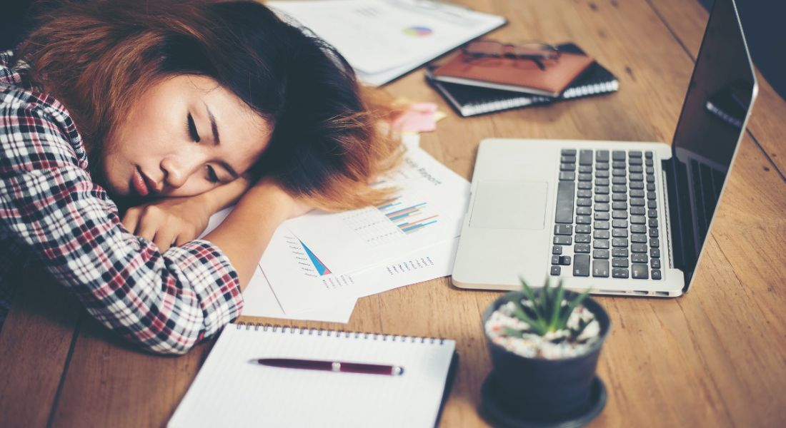 Young woman is sleeping on her desk by a laptop, showing signs of fatigue.
