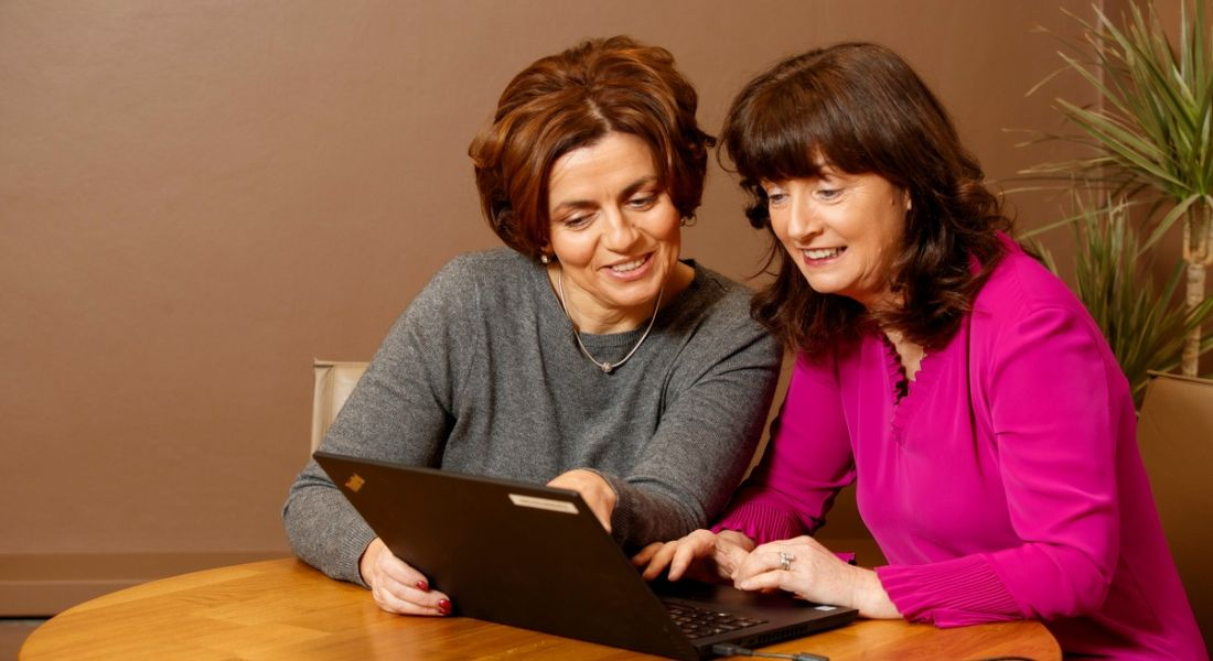 Two professional women are smiling and working together on a shared laptop in a corporate setting.