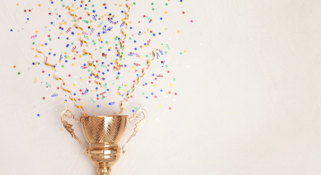 Trophy and confetti on light background, celebrating the best jobs announcement.