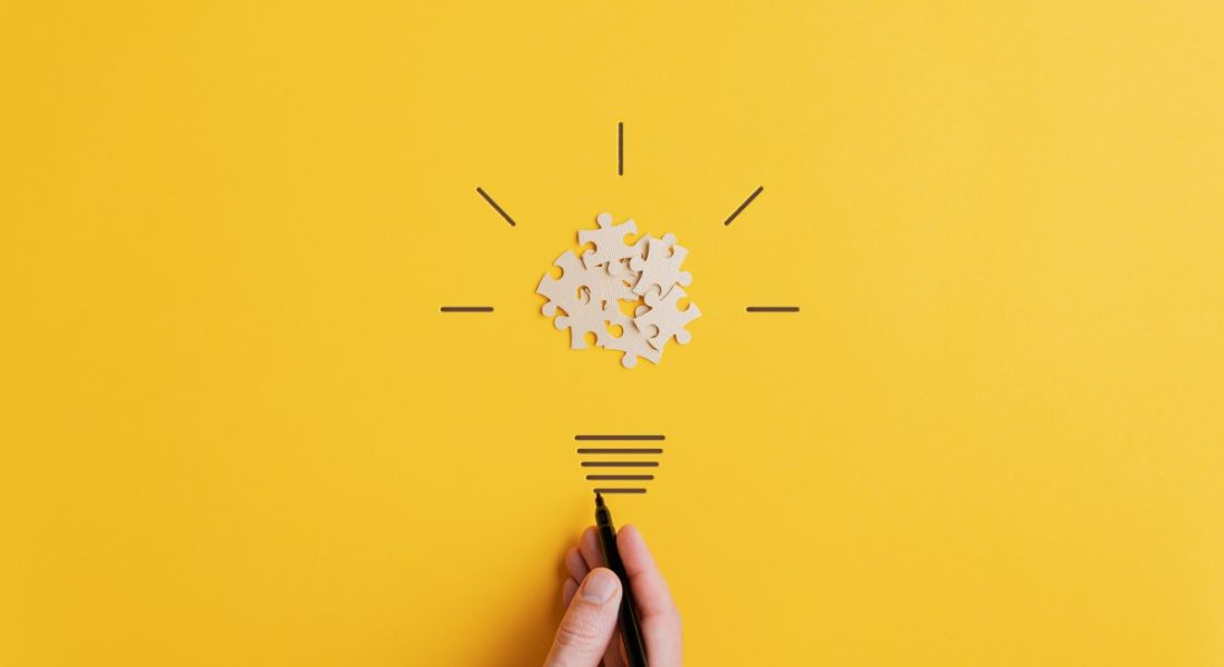 Hand drawing a light bulb of blank puzzle over yellow background.