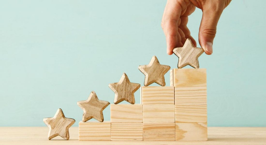 A hand is placing five stars in a row along stepped wooden blocks that are sitting on a wooden table.