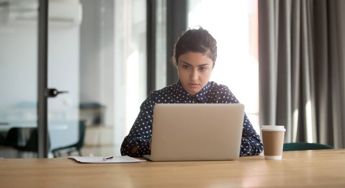 Professional woman concentrating on her laptop in an office.