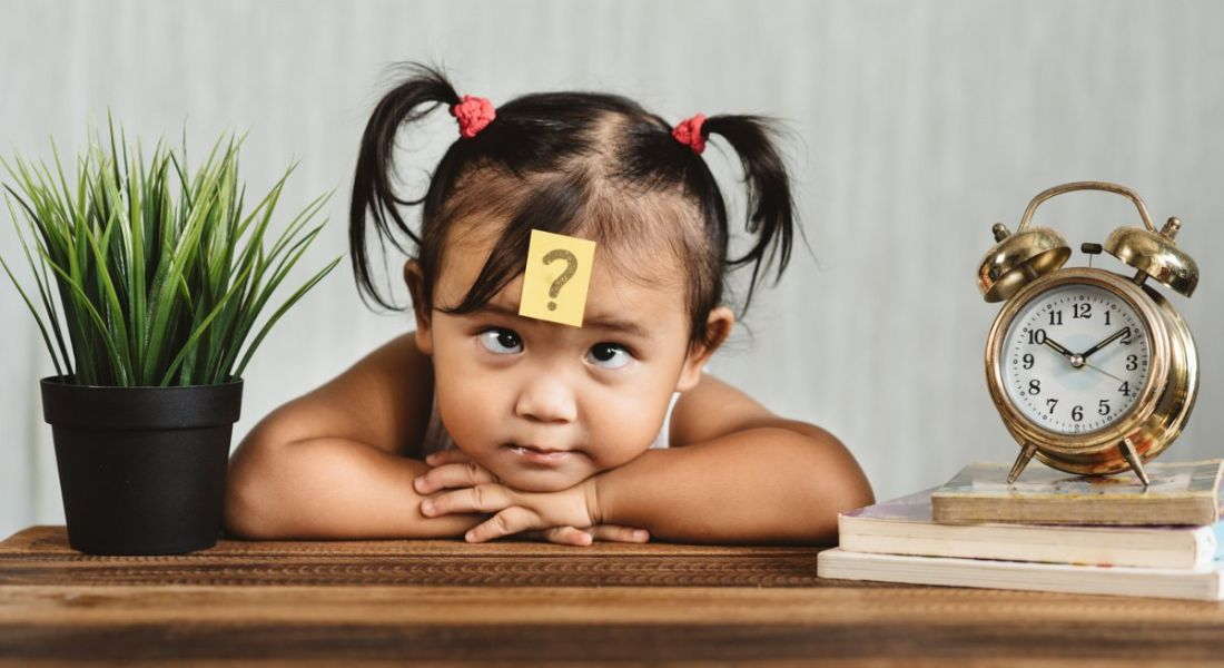 Cute and confused looking toddler with question mark on a post-it note on her forehead.