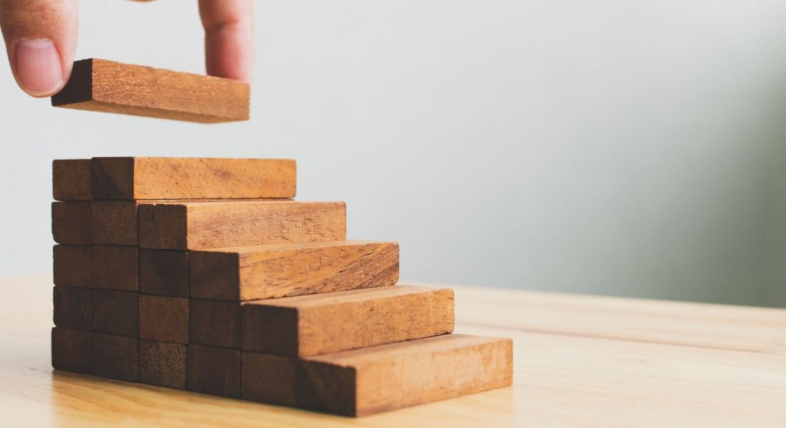 Hand arranging wood block stacking as steps.