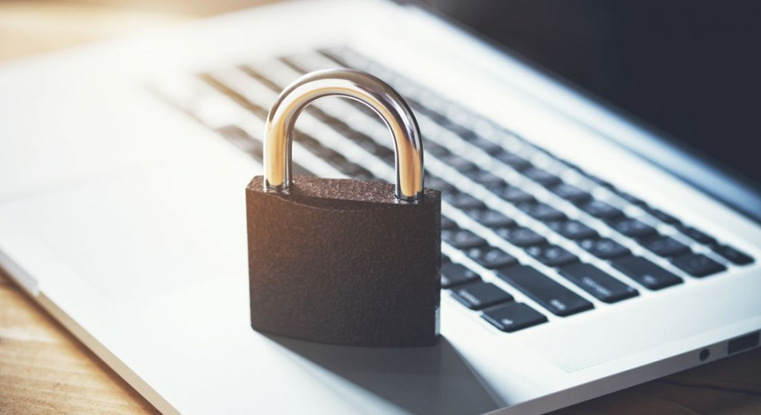 A padlock sitting on the keyboard of a laptop.