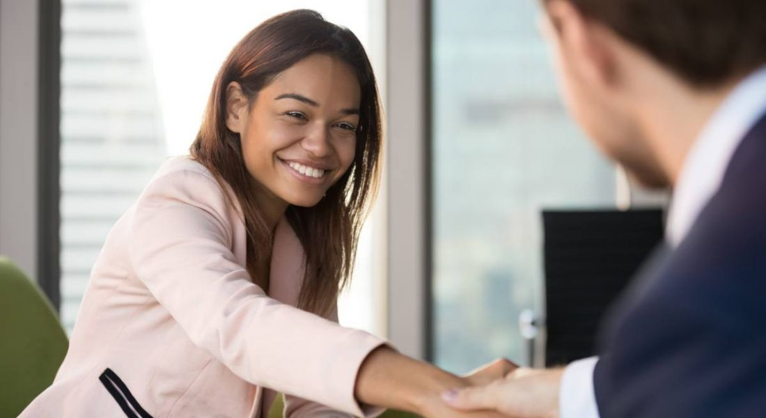 A young professional woman is shaking hands with a professional man in an interview setting.