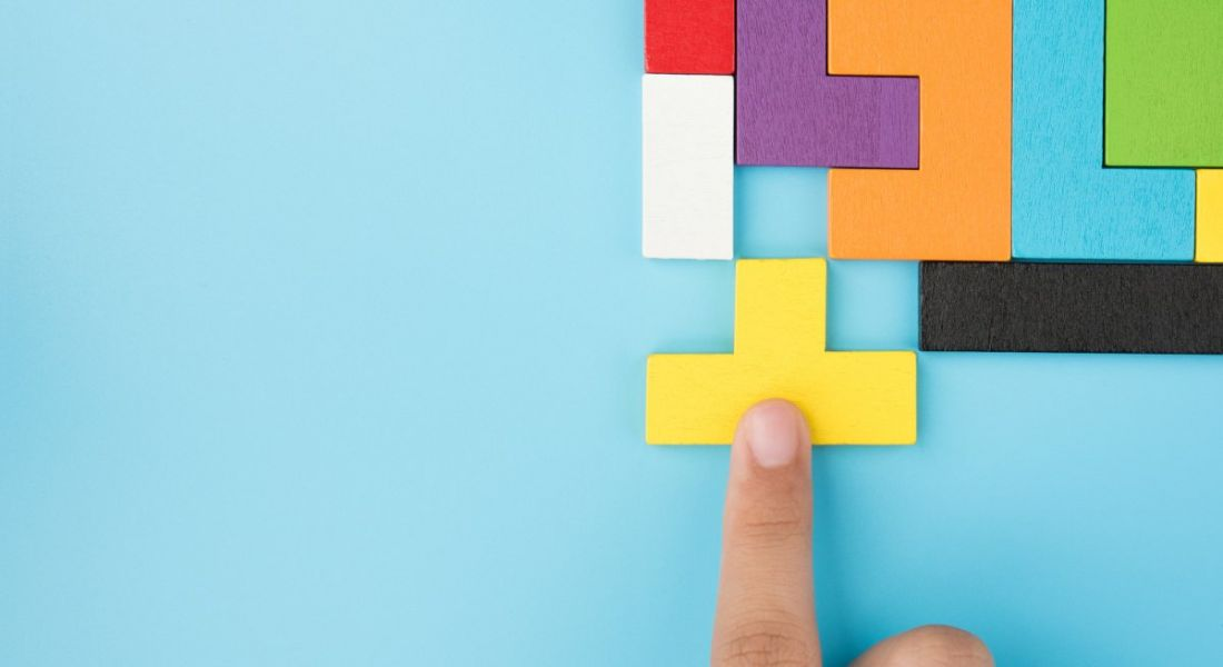 A finger is pushing the last piece of a multi-coloured jigsaw into place.