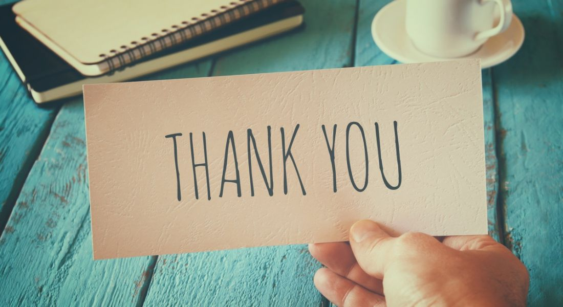 A person's hand is holding a piece of paper with thank you written on it.
