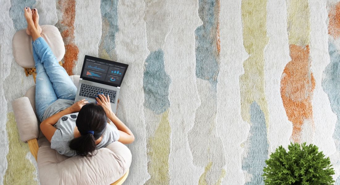 Woman remote working using a laptop from a comfortable chair, which is on a colourful carpet.