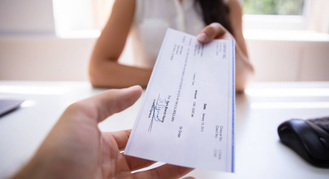 A person is handing a colleague their salary cheque across an office desk.