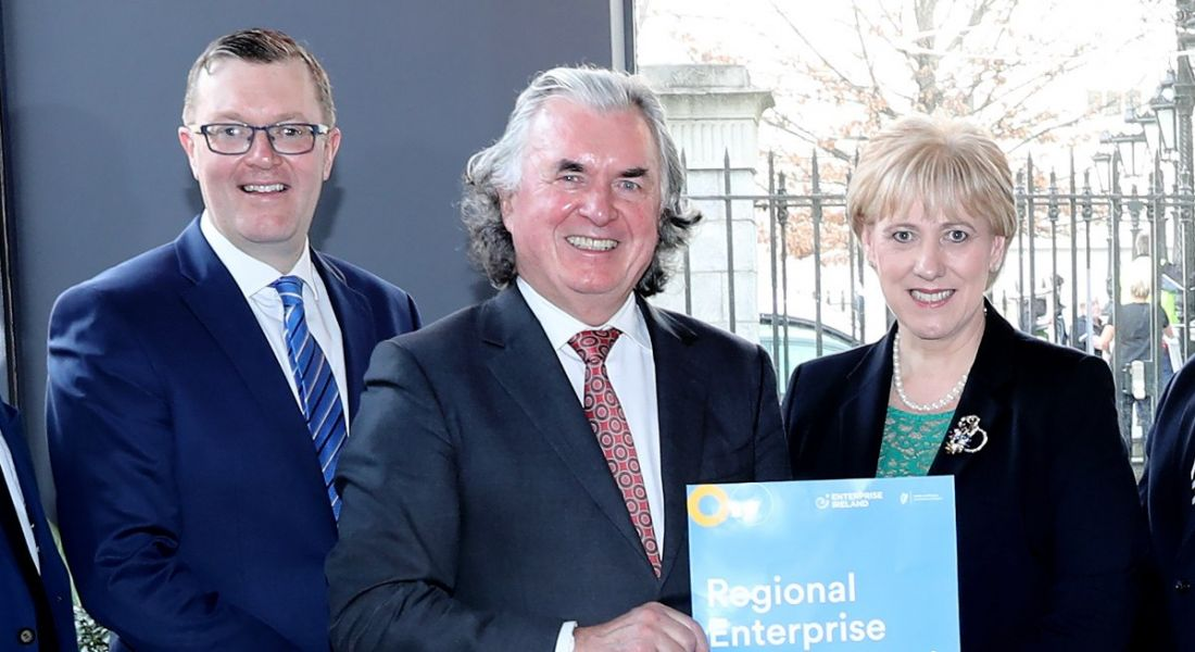 Two professional men and one professional woman are smiling into the camera at a corporate event and holding a document that reads 'regional enterprise development'.