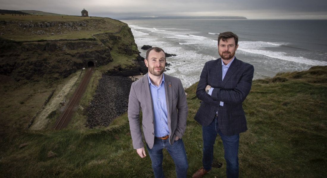 Lee Stuart and Jim Campbell from Covernet are standing on cliffs on the Irish north-west coast and looking into the camera.