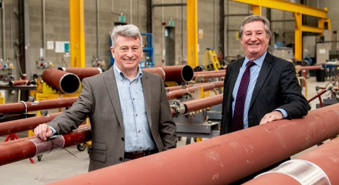 Two men in suits are smiling into the camera in a manufacturing room with large pipes.