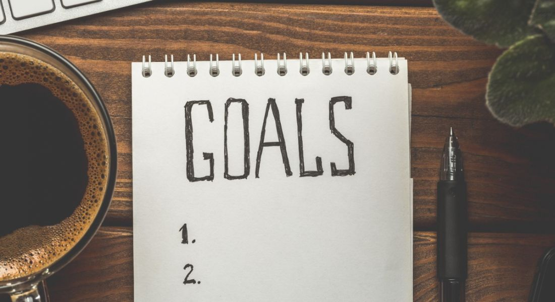A notepad with 'goals' written on it, beside a cup of coffee and a pen on a wooden desktop.