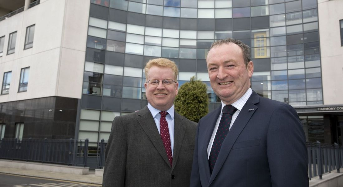Peter Rose and Nick Connors from Tekenable are standing outside a modern building in Dublin, smiling into the camera.