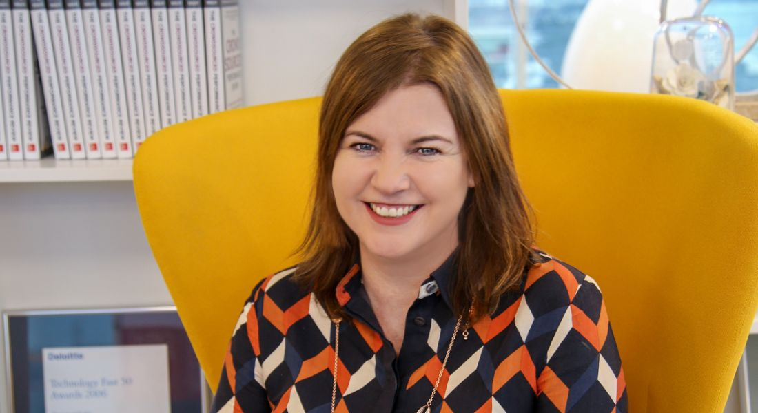 Workhuman's Michelle McDaid is sitting on a bright yellow chair and smiling into the camera at the company's Dublin office.