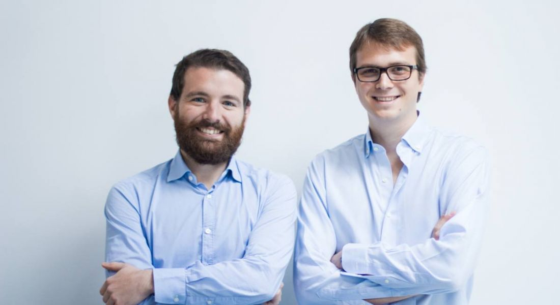 The co-founders of LogoGrab are standing together and smiling into the camera.