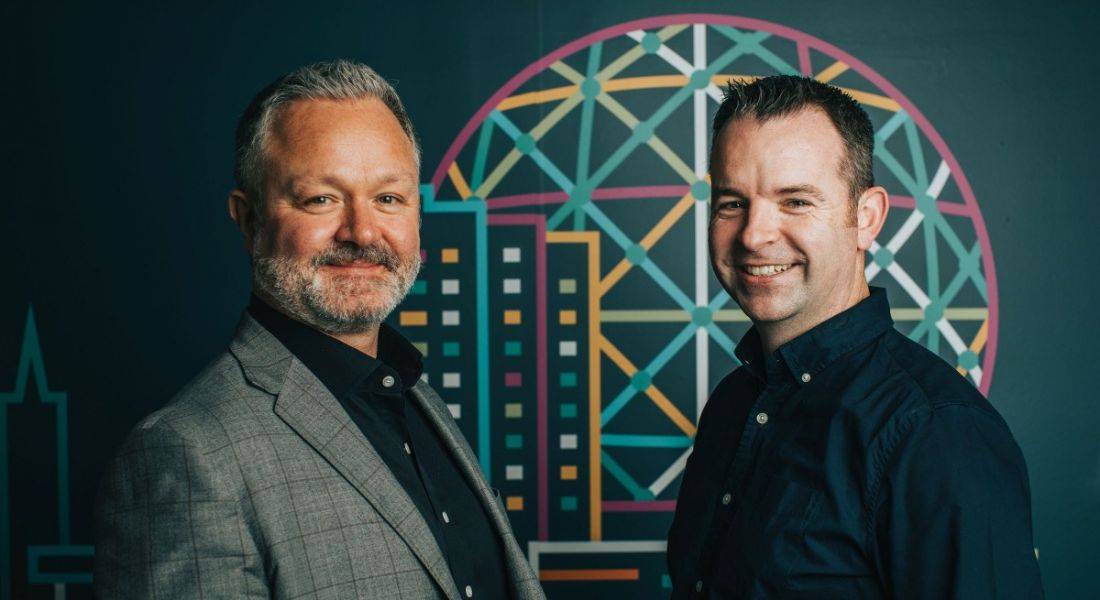 Two senior employees from Bazaarvoice are smiling into the camera, standing against a colourful background.