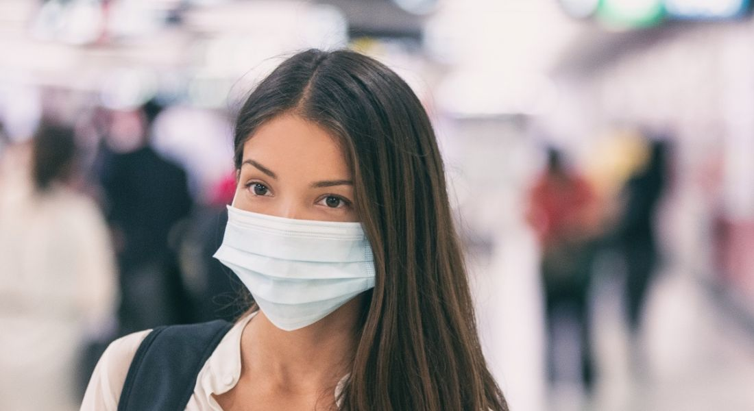 A young woman with a surgical mask over her face to protect her from coronavirus. A busy area is blurred out behind her.