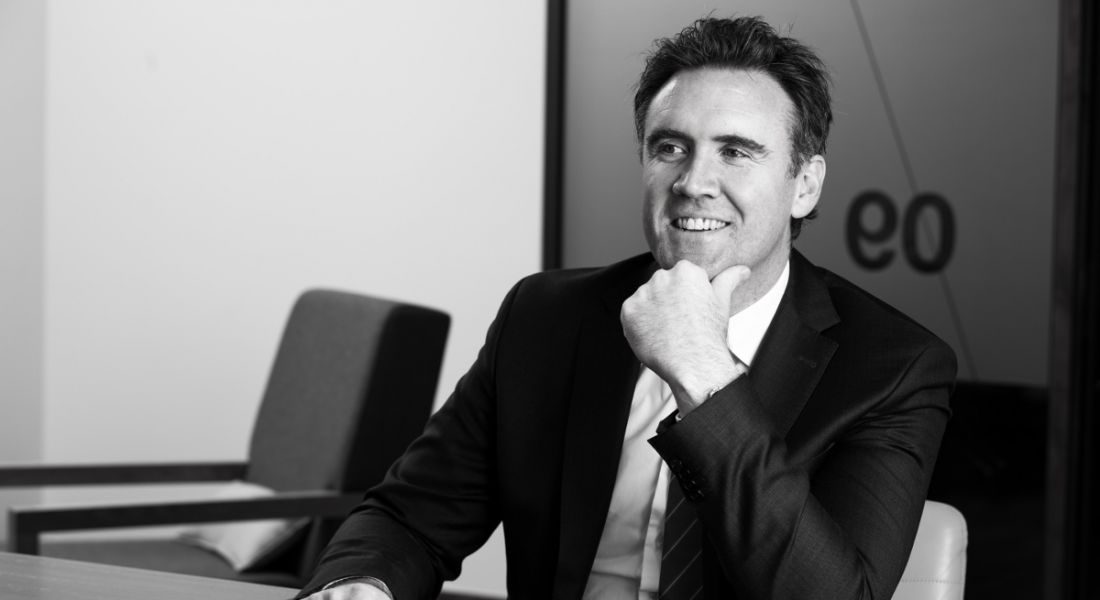 Black and white photo of Danny Buckley of EY in a suit, smiling at someone off camera.