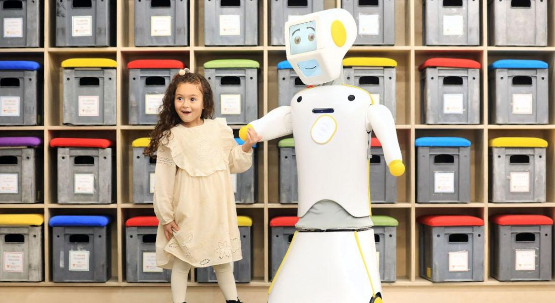 For Engineers Week, a young girl with dark hair excitedly holds the hand of a white and yellow robot, who is smiling.