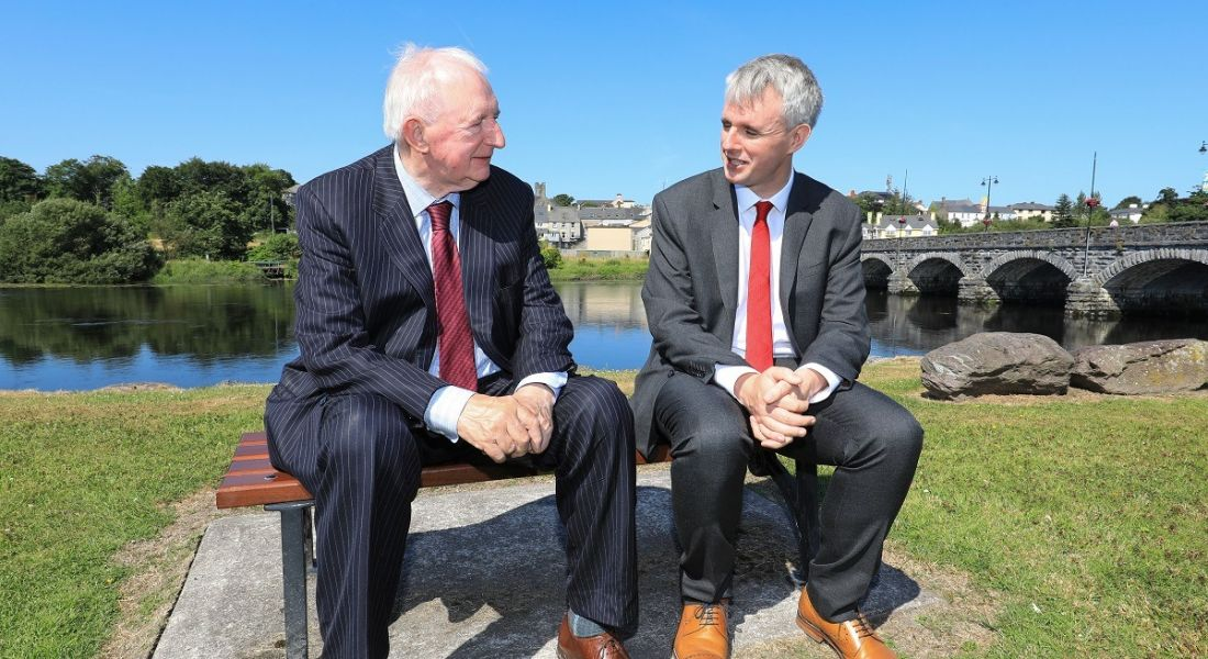 Brian McCarthy and Denis McCarthy sitting on a stone bench chatting in suits with a river and bridge behind them.