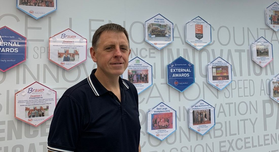 Richard Cribbin is smiling into the camera in front of a wall of company awards in an office.