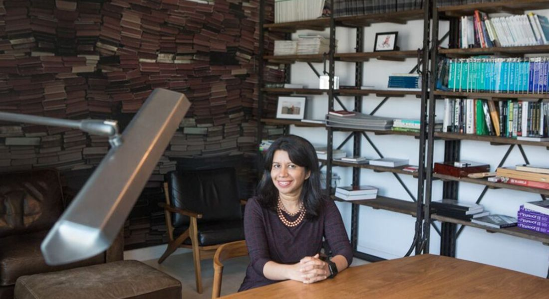 A smiling woman with dark hair sitting at a wooden table. Behind her are shelves of books. She is Rashi Khurana, VP of engineering at Shutterstock.