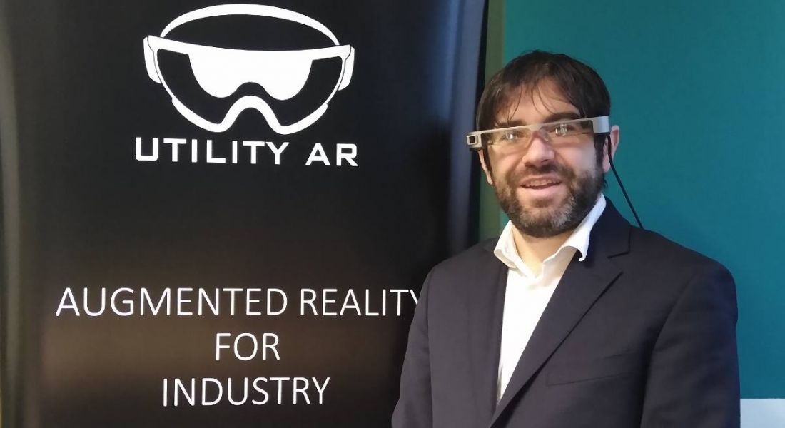 Patrick Liddy of UtilityAR is wearing AR glasses and smiling into the camera beside a pop-up stand with the company's branding on it.