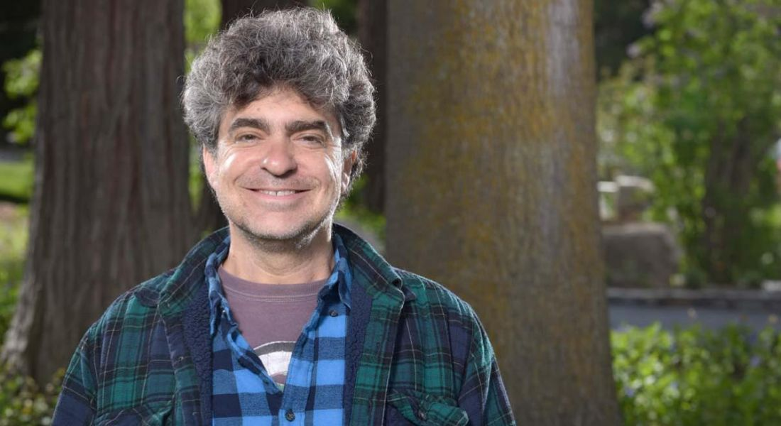 Remote-first company leader Paul Hershenson is standing in a wooded area and smiling into the camera in casual clothing.