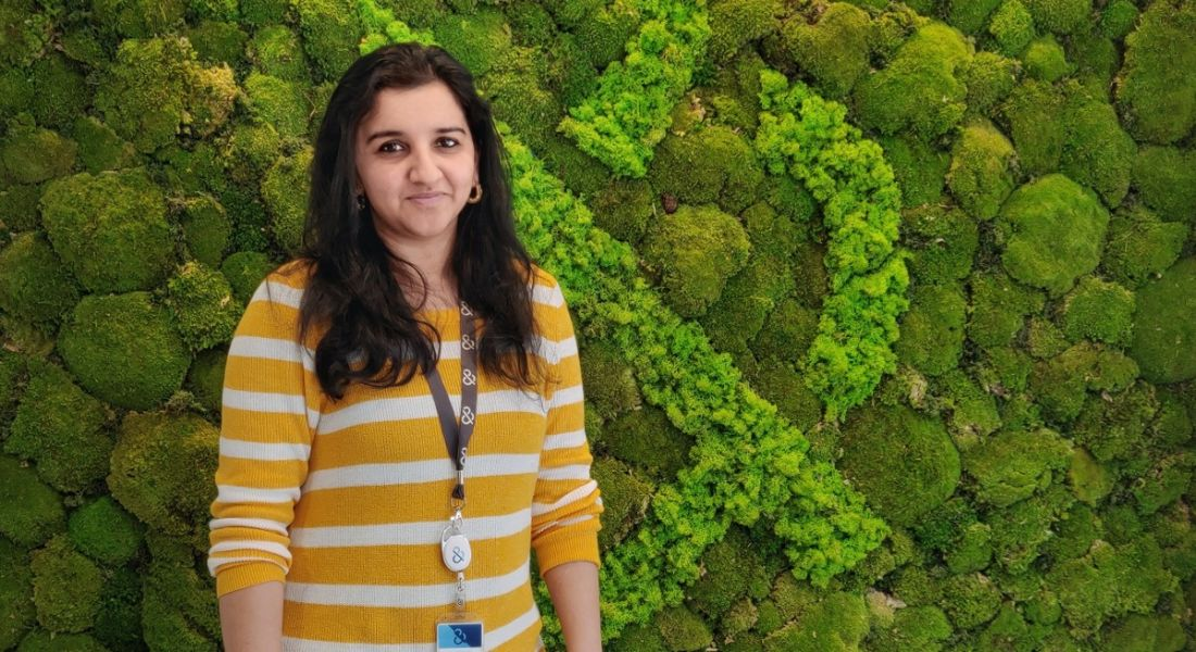 QA lead Srirekha Krishnan of Dun & Bradstreet is standing against a green wall of foliage in a bright yellow jumper and smiling into the camera.