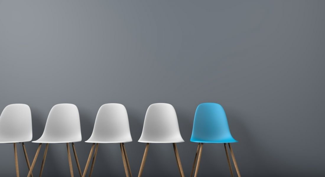 Five chairs are in a row against a grey background, with four coloured white and one coloured blue.