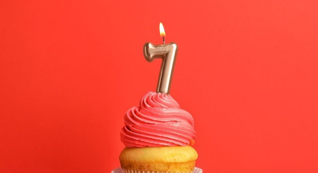 Birthday cupcake with a number seven candle, against a red background.