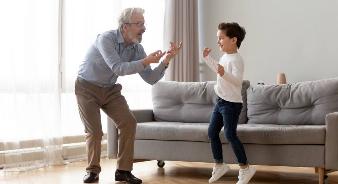 A young boy and his grandfather are dancing in a sitting room.