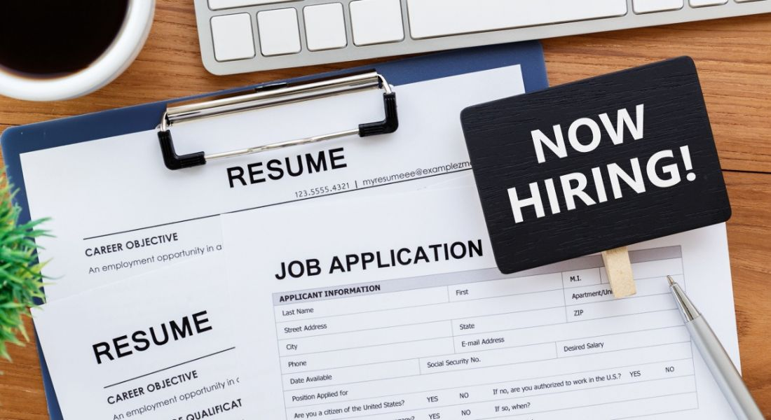A job application and resumé on a desk beside a small sign saying Now Hiring.