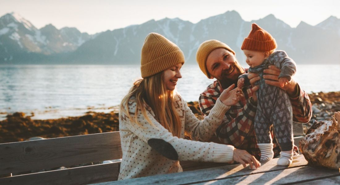A young family of a woman and a man are interacting with their small child outside in a scenic setting.