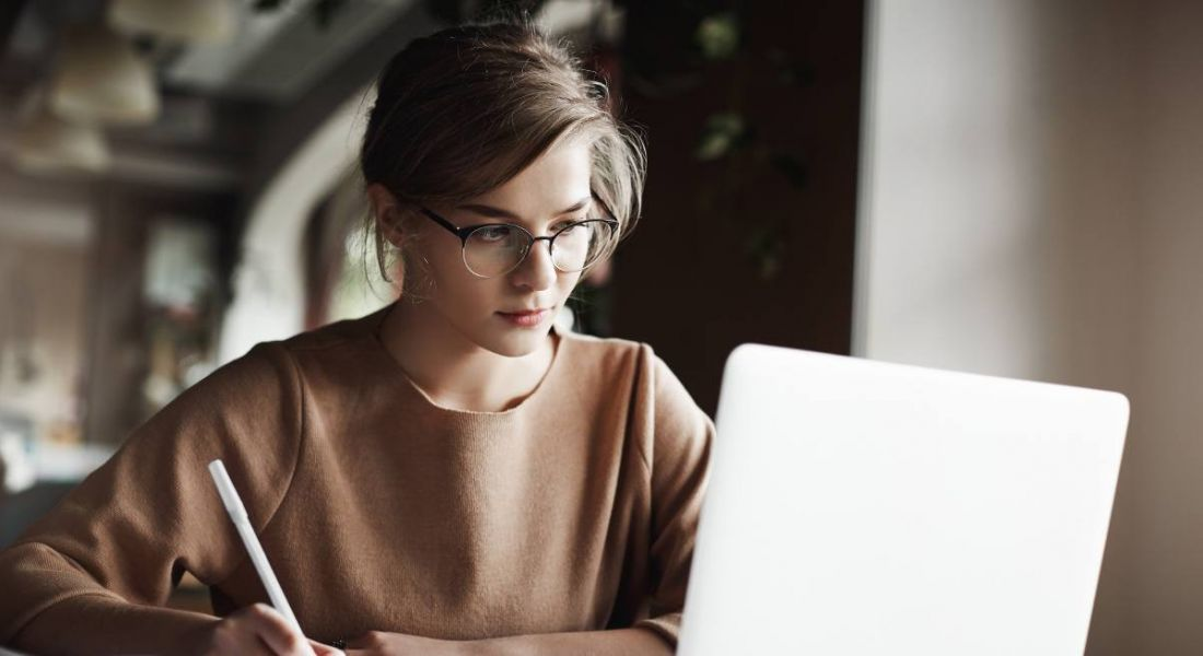 A young woman wearing glasses is writing something down while looking at a laptop.