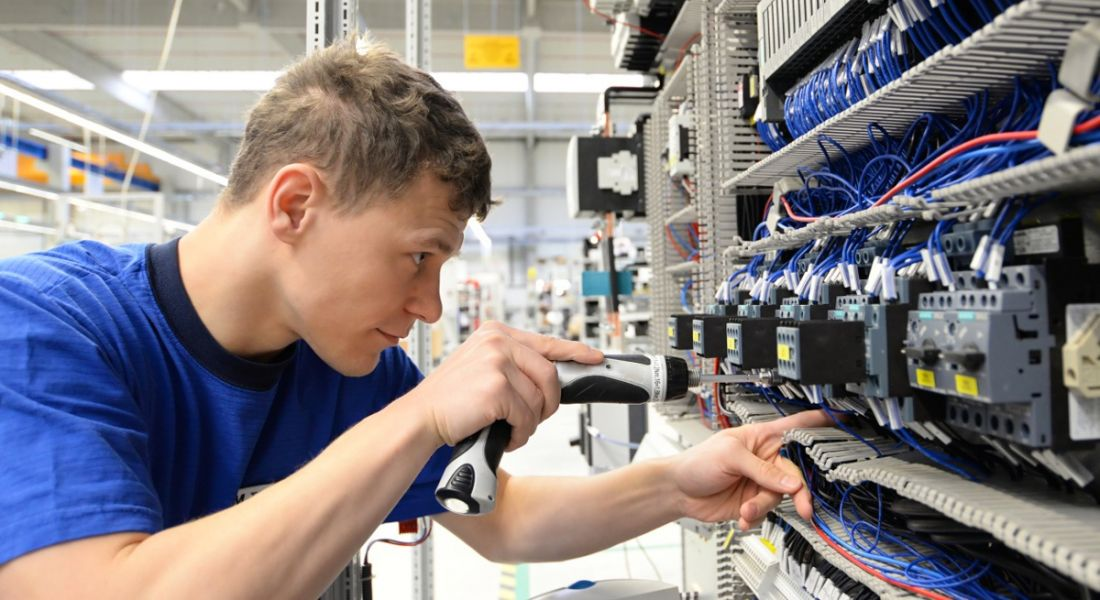 A young man is working on a fuse box.