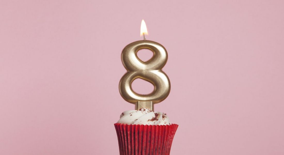 Number 8 gold candle in a cupcake against a pastel pink background.