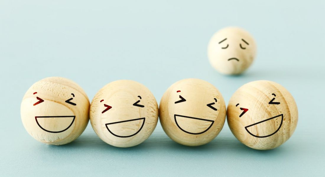 Four wooden balls with happy faces drawn on. A fifth one with a sad face is in the background, representing imposter syndrome.