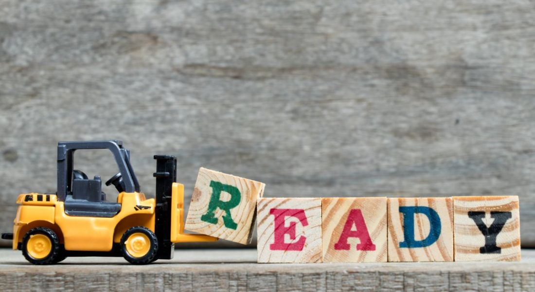 Yellow plastic forklift adding the letter R to complete word 'ready' on wooden blocks.