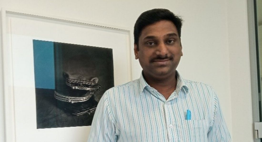 Kaarthik Janakiraman is standing in an office, wearing a striped shirt and smiling into the camera.